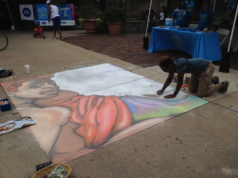 man drawing with sidewalk chalk in Dayton, Ohio