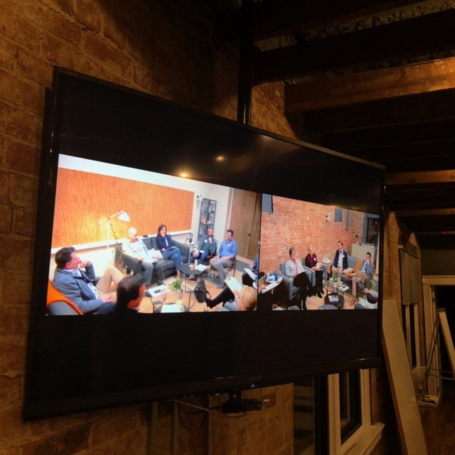 A tv mounted to a wall displaying two other groups of people from different locations during a video conference.